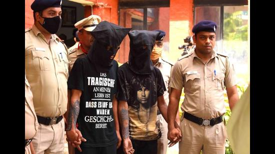 The accused, a cook and a car washer, in police custody in Chandigarh on Friday. (HT Photo)