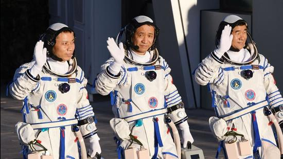 In this file photo, Chinese astronauts Nie Haisheng (C), Liu Boming (R) and Tang Hongbo wave during a departure ceremony before boarding the Shenzhou-12 spacecraft on a Long March-2F carrier rocket at the Jiuquan Satellite Launch Centre in the Gobi desert in northwest China. The three astronauts have completed the country's longest crewed mission and returned to Earth. (AFP)