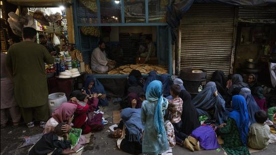 Afghan women and children sit in front of a bakery waiting for bread donations in Kabul's Old City. The UN Security Council on Friday unanimously extended the mandate of the UN assistance mission in Afghanistan for six months. (AP)