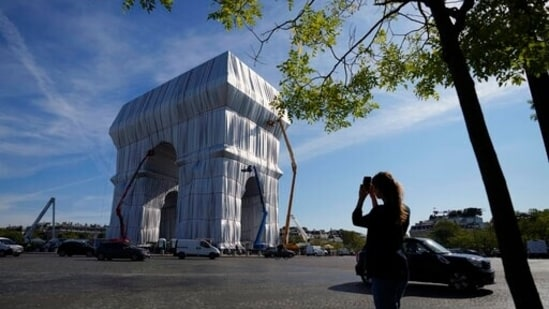 """Onlooker takes a picture as workers put the final touch to wrap the Arc de Triomphe monument, in Paris. The """"L'Arc de Triomphe, Wrapped"""" project by late artist Christo and Jeanne-Claude will be on view from, Sept. 18 to Oct. 3. The famed Paris monument will be wrapped in 25,000 square meters of fabric in silvery blue and with 3,000 meters of red rope.(AP Photo/Francois Mori)"""