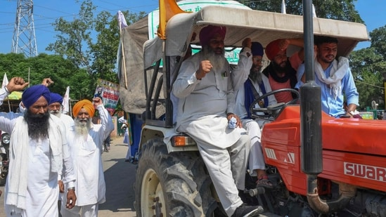 Farmers shout slogans as they make their way to Delhi to join farmers who are continuing their protest against the central government's agricultural reforms in the village Jandiala on the outskirts of Amritsar on September 15, 2021.(AFP)