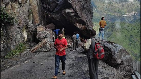 People crossing the boulders which blocked the NH-5 after a massive landslide at Chaura in Kinnaur, HP, on Friday. (HT Photo)