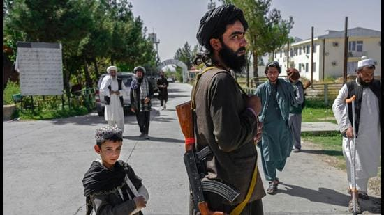 An Afghan boy stands next to a member of the Taliban in front of the Pul-e-Charkhi prison in Kabul. Afghanistan needs the assistance of the international community, especially help from its neighbours, Xi Jinping said. (AFP)