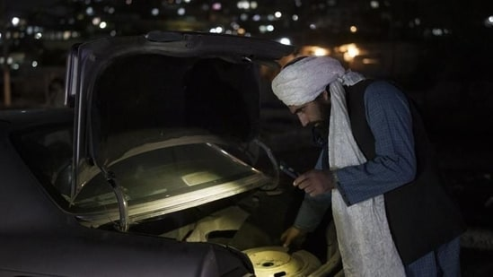 A Taliban fighter checks the trunk of a car at a checkpoint in Kabul, Afghanistan.(AP file photo)