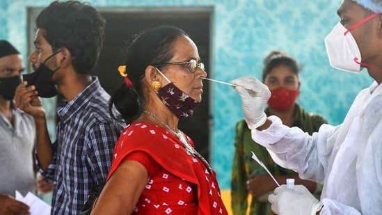 A health worker takes samples from a woman in Maharashtra. (Satish Bate/HT PHOTO)