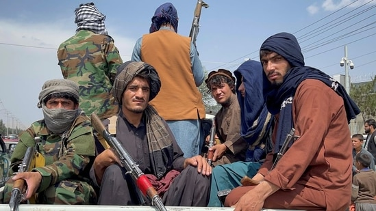 Taliban forces patrol near the entrance gate of Hamid Karzai International Airport in Kabul, Afghanistan.