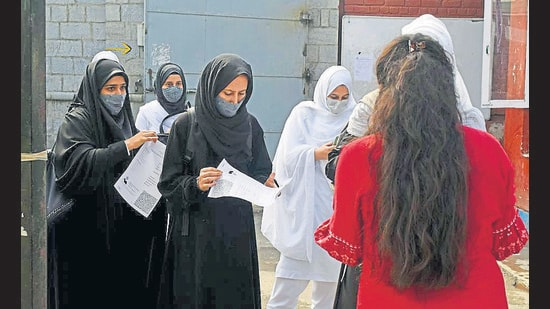 Students produce their vaccination certificates before entering a college premises in Srinagar on Monday. (ANI)