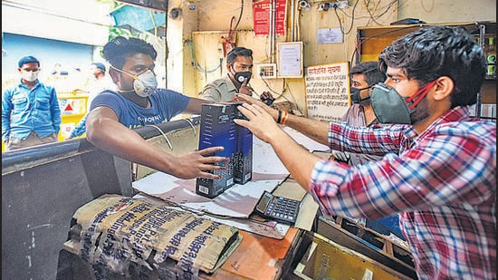 People purchase liquor from a shop at Kalyanpuri, during lockdown, last year. At least 23 wards in Delhi will have no liquor shop open since liquor licences will stay suspended between October 1 and November 16, for smooth transition under the new excise policy regime. (Amal KS/HT PHOTO)