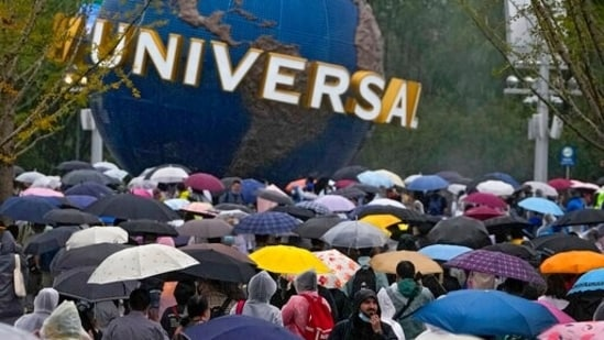 People wearing raincoats and carrying umbrellas walk through a plaza near the entrance of Universal Studios Beijing in Beijing, Monday, Sept. 20, 2021. Thousands of people brave the rain visit to the newest location of the global brand of theme parks which officially opens on Monday.(AP Photo/Andy Wong)