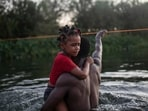 A Haitian migrant carries a child while wading across the Rio Grande from Del Rio, Texas, to return to Ciudad Acuña, Mexico, on Sept. 19. Of the roughly 1.8 million Haitians living outside their homeland, the United States is home to the largest Haitian immigrant population in the world, numbering 705,000 people from the Western Hemisphere's poorest country, AP reported.(Felix Marquez / AP)