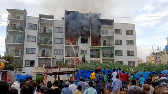 Locals gather as firefighters douse a fire that broke out at a private apartment following a gas leakage in the pipeline in Bengaluru on Tuesday. (ANI)