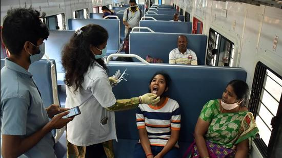 A healthcare worker collects a swab sample of a girl for the Covid test inside a train compartment, in Bengaluru, Karnataka. (ANI)