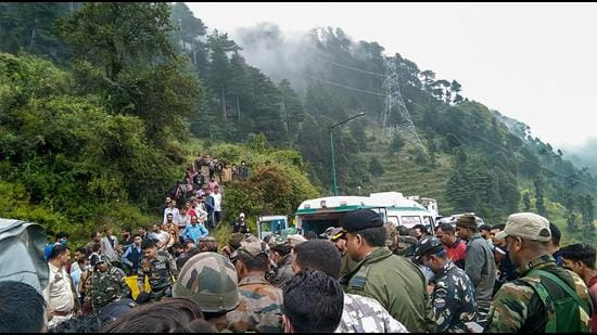 Police personnel and locals at the site where an Indian Army helicopter crashed in Udhampur district on Tuesday. (PTI)