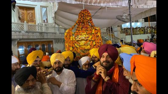 Punjab chief minister Charanjit Singh Channi (left) and state Congress president Navjot Singh Sidhu carrying the Palki Sahib at the Golden Temple in Amritsar early on Wednesday. (Sameer Sehgal/HT)