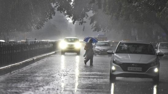 A person crosses the road during rain at Janpath on Tuesday.(Raj K Raj/HT Photo)
