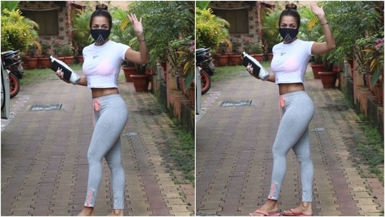 Malaika's tights came in a grey shade and featured a contrasting neon orange piping and drawstring detail. She rounded off her workout look with a black printed face mask and neon orange flip flops.(HT Photo/Varinder Chawla)