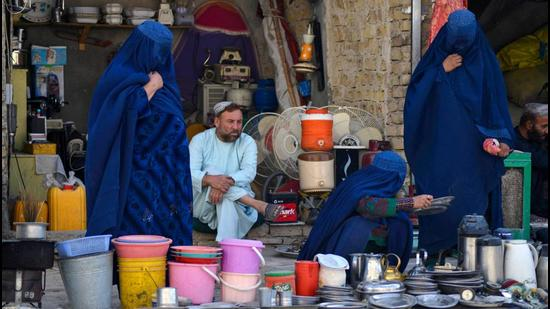 Women look at household items at a stall in a market in Kandahar, Afghanistan on Wednesday. Economic sanctions against Afghanistan must end and unilateral restrictions should be lifted as soon as possible, Chinese state councillor and foreign minister Wang Yi has said. (AFP)