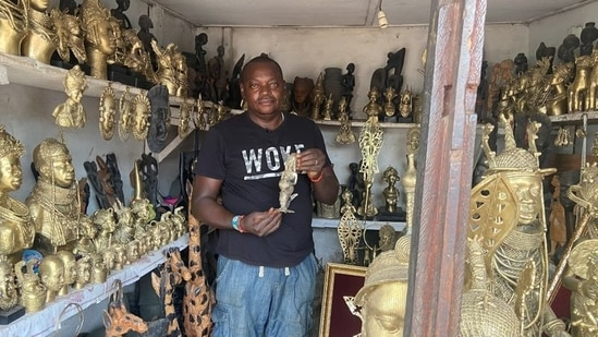 Edosonmwan William, bronze caster, is seen with one of his works inside is gallery at Igun street, Benin City, Nigeria