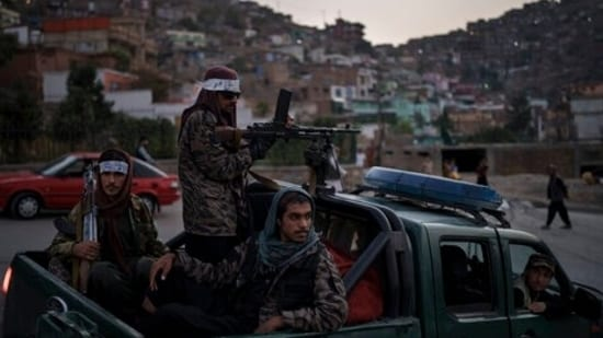 Taliban fighters sit on the back of a pickup truck as they stop on a hillside in Kabul, Afghanistan.(AP)