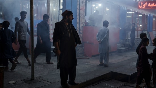 A Taliban fighter stands in the corner of a busy street at night in Kabul.