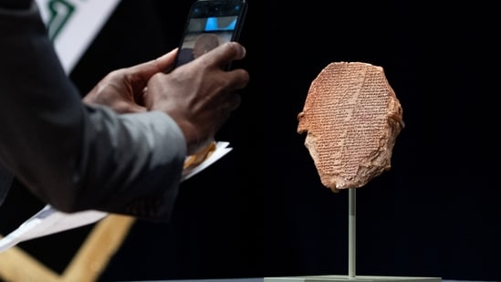 A man photographs the Gilgamesh Tablet, a 3,500-year-old Mesopotamian cuneiform clay tablet that was believed to be looted from Iraq around 1991 and illegally imported into the US to be displayed at the Washington Museum of the Bible, during a ceremony to repatriate the tablet to Iraq, at the Smithsonian National Museum of the American Indian, in Washington, DC,(Photo by SAUL LOEB / AFP)