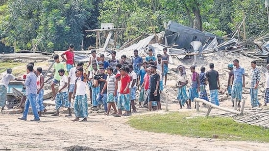 Villagers near their houses which were demolished during an eviction drive, at Gorukhuti in Darrang district, on Friday. (PTI)