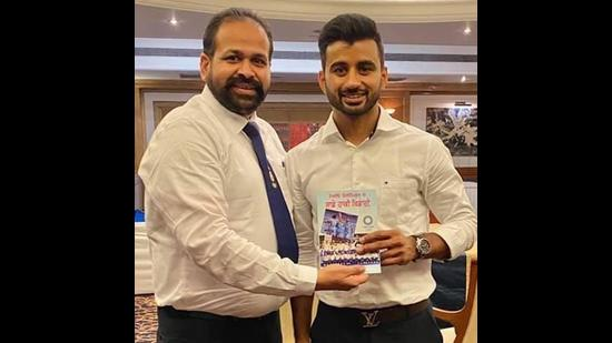 Author Navdeep Singh Gill presenting his book to Manpreet Singh, captain of the Indian hockey team which won a bronze medal at the Tokyo Olympics. (HT photo)