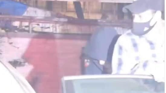 Shah Rukh Khan hides his face behind a hoodie.