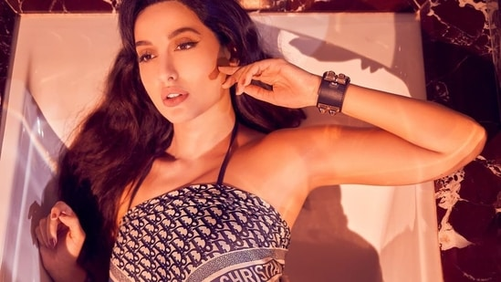 Nora Fatehi teamed the scarp crop top with a bikini bottom that came with a low-waisted style and featured adjustable side ties for an ideal fit.(Instagram/norafatehi)