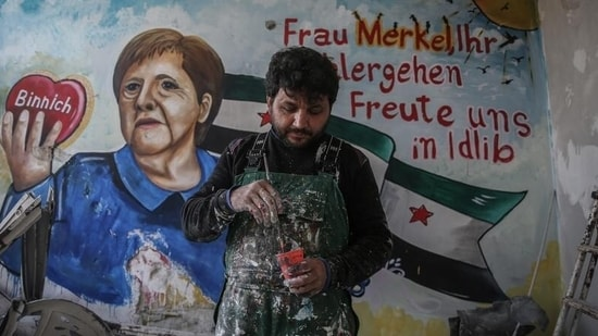Amsar in front of the mural of Angela Merkel that he painted in March 2020(Anas Alkharboutli/dpa/picture alliance)
