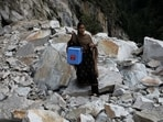 Kanta Devi, 26, a health worker, carries a box containing Covishield vaccines, as she walks through a road that was blocked after a landslide, near Malana village in Himachal Pradesh, on September 14. To vaccinate the villagers of Malana, one challenge to overcome by health workers was the steep topography, moreover to walk on it for hours and another was religious beliefs, as the tourism-dependent state immunised its roughly 5 million adults, Reuters reported.(Adnan Abidi / REUTERS)