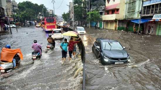 Vehicles wade through a waterlogged road in Hyderabad following heavy rain on Monday.(PTI Photo)