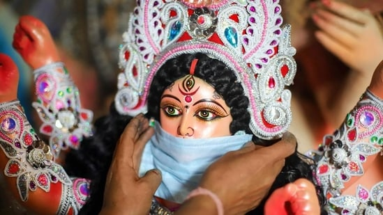 A devotee puts a mask on the face of a Goddess Durga idol to aware people against Covid-19.(PTI Photo)
