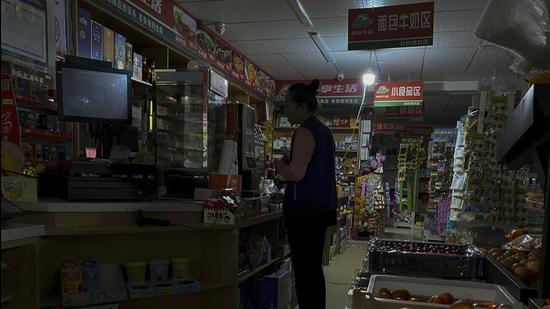 A woman buys groceries from a mini market using a light bulb powered by gasoline generator during a blackout in Shenyang in northeastern China's Liaoning Province. Provinces and regions including Liaoning and Jilin in northeast China, the trading powerhouse Guangdong in the south and Zhejiang in the east have been in the grip of power shortage for weeks now. (AP)