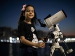 Brazilian 8-year-old astronomer Nicole Oliveira poses for a picture with her telescope in Fortaleza, Brazil.(AFP)