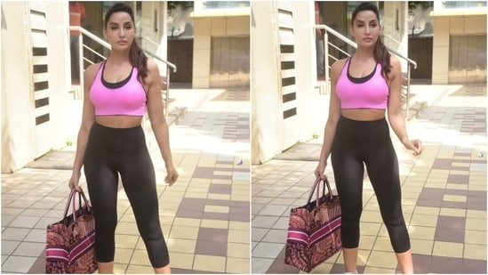 Nora was pictured outside of her gym class today in Mumbai, and for the outing, she chose a noteworthy athleisure look - a hot pink sports bra paired with a set of leggings.  The hot pink and black sports bra with a scoop neck and wide straps brightened up her workout look.  (HT Photo / Varinder Chawla)