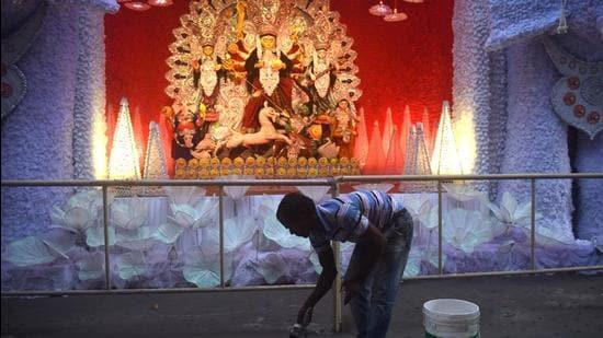 A man paints a social distancing mark at Durga Puja pandal in Kolkata, West Bengal. (HT Photo)