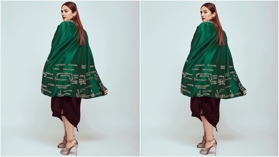 Huma's look for the photoshoot features a black spaghetti-strapped slip dress with a flowy silhouette and an asymmetric hem with tie detail on one corner. She paired the classic black ensemble with a notch lapel silk cape jacket adorned with slits to pull the arms out and hymns printed in white shade.(Instagram/@iamhumaq)