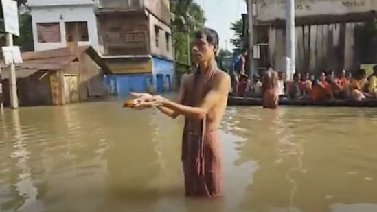 Arup Bera – a resident of Ward 2 of the Ghatal municipality area – was seen traversing the flooded streets near his home to offer 'tarpan' on Mahalaya