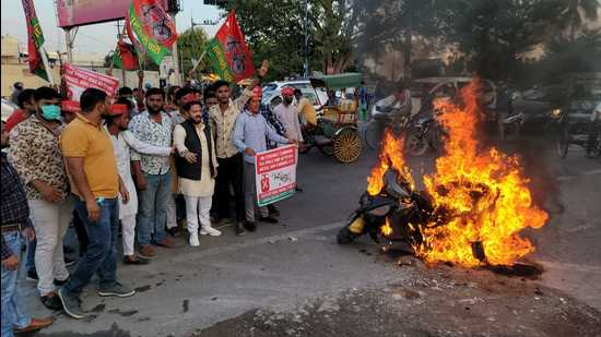 Rizwan Raisuddin 'Prince' (in black jacket), the vice president of Agra unit of Samajwadi Party burning scooter to protest hike in fuel prices in Agra on Friday. (HT photo)