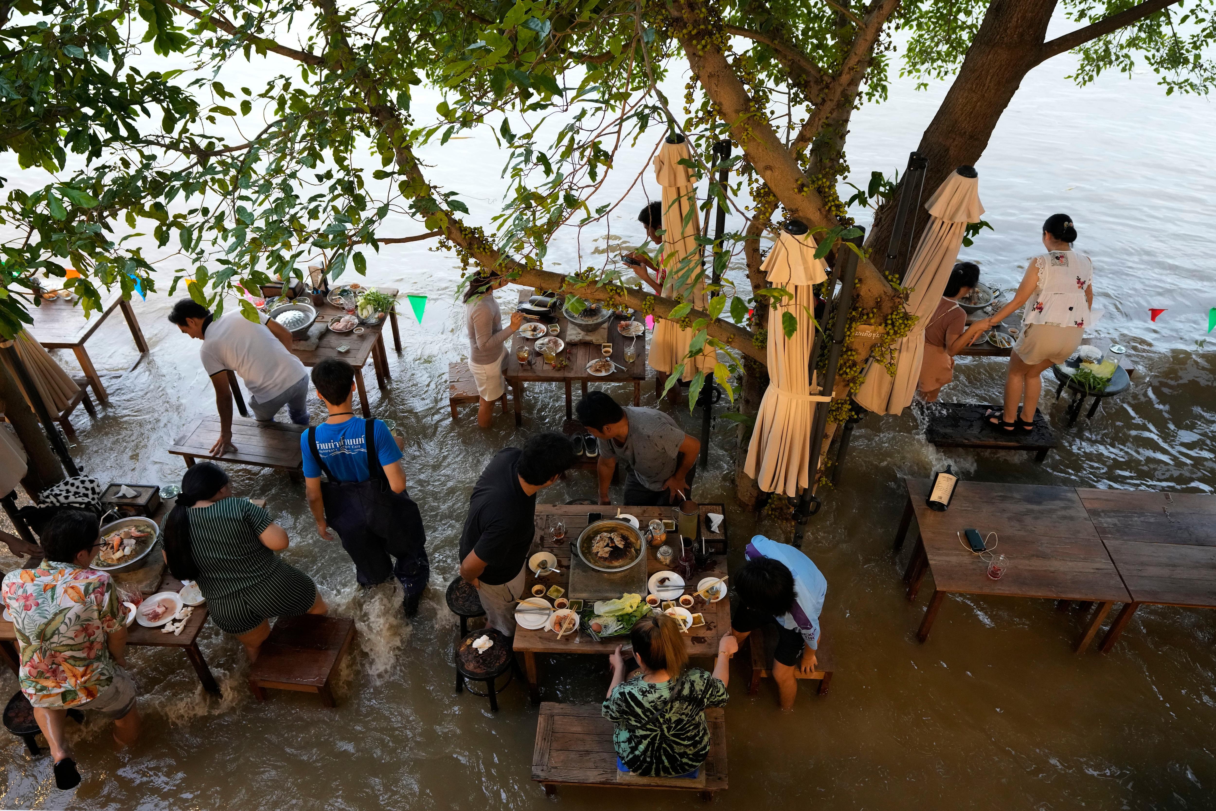 नदी के किनारे स्थित चौप्रया एंटीक कैफे के ग्राहक नाव के उठने पर प्रतिक्रिया करते हैं क्योंकि वे नोंथबुरी (एपी) में चाओ फ्राया नदी में असाधारण उच्च जल स्तर का आनंद लेते हैं।
