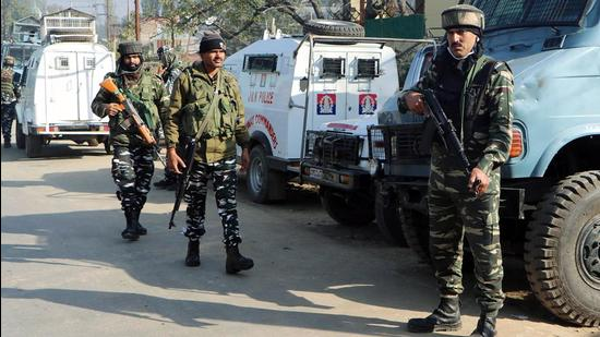 Security personnel stand guard as the National Investigation Agency (NIA) carry out raids in Anantnag on Sunday. (ANI PHOTO.)