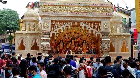 Devotees take pictures of a puja pandal ahead of the Durga puja festival, in Kolkata on Sunday. (ANI Photo)