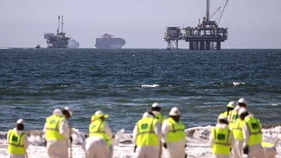 Cleanup workers search for contaminated sand and seaweed in front of drilling platforms and container ships about one week after an oil spill from an offshore oil platform. The heavy crude oil spill affected close to 25 miles of coastline in Orange County. Huntington Beach is open but the public is not allowed to enter the water.(Mario Tama/Getty Images/AFP)