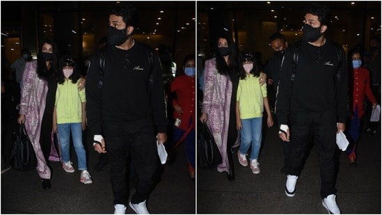 Abhishek was snapped outside the airport with his family in a black crewneck sweatshirt, which he teamed with matching joggers and a black face mask. The actor completed his airport look with white chunky lace-up sneakers.(HT Photo/Varinder Chawla)