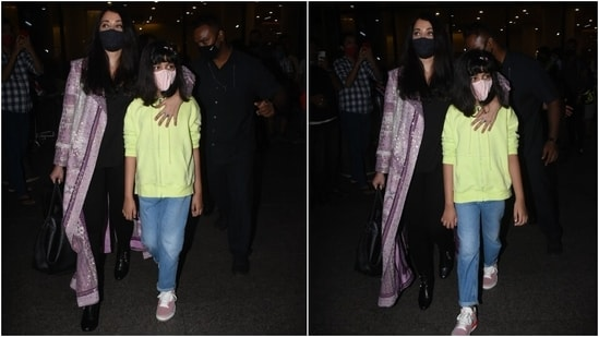 As for Aishwarya, she looked stunning in a solid black blouse and matching tights. She added a dash of colour to her look with a lavender embroidered long jacket. Black leather boots, a face mask, and a top handle bag completed her airport outfit.(HT Photo/Varinder Chawla)
