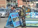 A security personnel stands guard at a check point, in Srinagar on Monday.(PTI Photo)