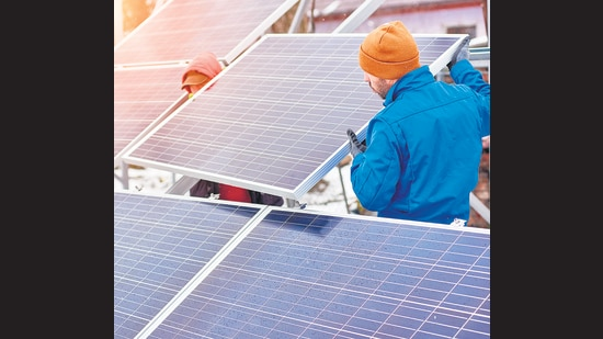 Technicians in blue suits mounting photovoltaic solar panels on roof of modern house. Building climate action into every new construction design is the need of the hour. (Shutterstock (FOR REPRESENTATIONAL PURPOSE))
