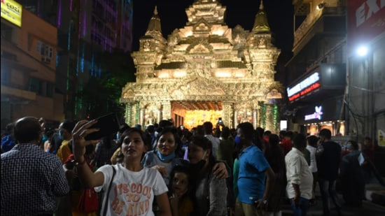Devotees take pictures at a puja pandal during the Durga puja festival in Kolkata. (HT photo.)