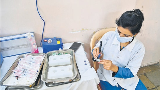 A health worker prepares a vaccine bottle for Covid vaccination in Pune. As of Tuesday, Pune district has reported 497 new Covid cases and six deaths due to the infection. (HT)